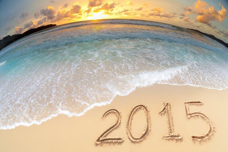 Overzeese die strandzonsondergang met 2015 nieuwe jaarcijfers wordt geschoten royalty-vrije stock afbeeldingen