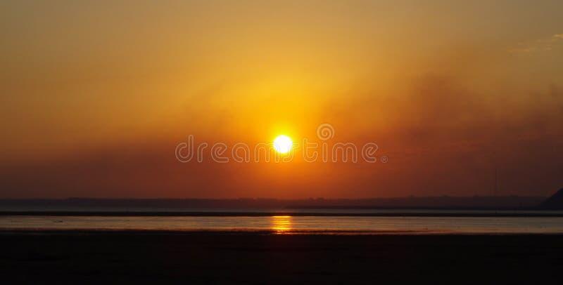 Overzeese eb gouden zonsondergang over het overzees en citythe de zon Overzees van Azov aardig Het Effect van de eb Mooie Zonsond royalty-vrije stock afbeeldingen