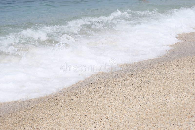 Overzeese golf met schuimbroodjes op de zandige kust Mooi Zeegezicht royalty-vrije stock fotografie