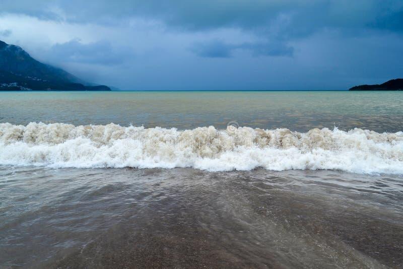 Overzeese golf in stormachtig weer De troebele golf Lage wolken over het kuststrand Van Montenegro in regenachtig weer Het overze stock foto