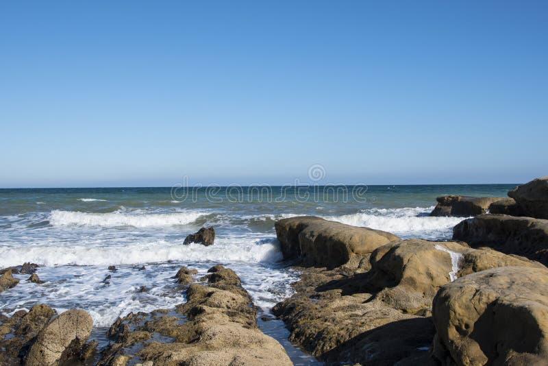 Overzeese golfschuim en rotsen op het strand in Estepona, Andalucia, Spanje Vreedzame oceaangolven bij strand royalty-vrije stock foto's