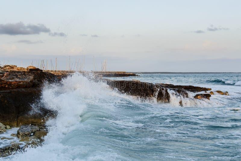 Overzeese golven die bij rotsen breken stock afbeeldingen