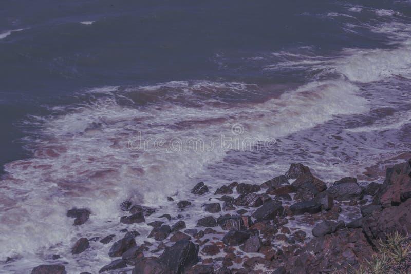 Overzeese golven die bruine rotsen raken stock afbeeldingen