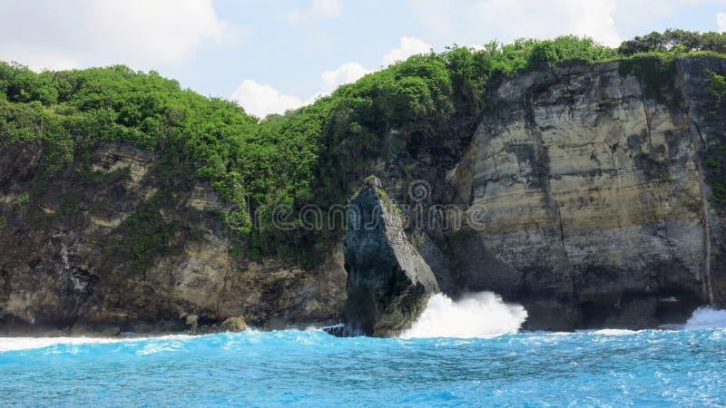 Overzeese golven die op een rots in het overzees dichtbij de rotsachtige kust van het eiland van Nusa Penida in Indonesië breken stock foto's