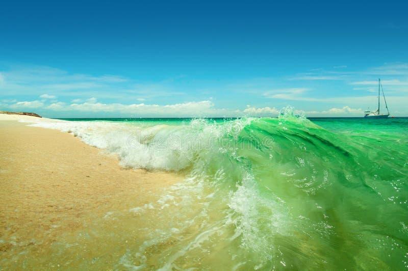 Overzeese golven die op het strand op een zonnige dag breken royalty-vrije stock afbeelding