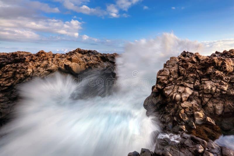 Overzeese golven die op rotsen breken royalty-vrije stock afbeelding