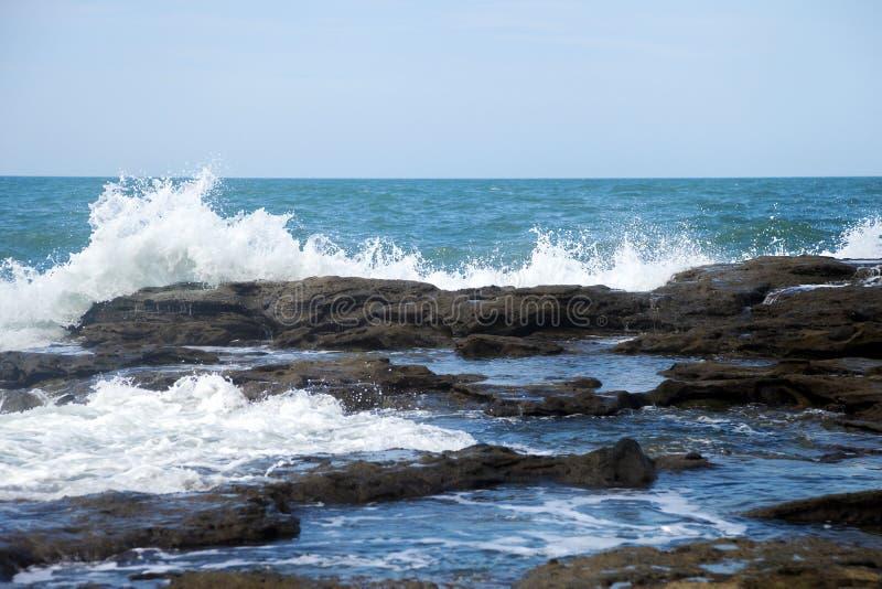 Overzeese golven die in rotsen verpletteren stock afbeelding