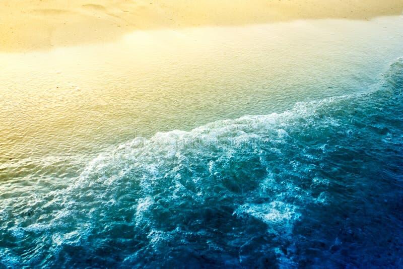 Overzeese golven met gouden zand stock foto's