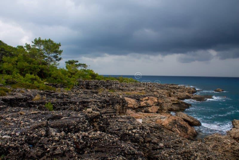 Overzeese golven op rotsachtig strand tussen rotsen stock fotografie