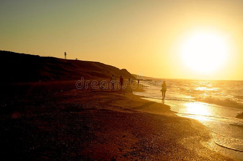 Overzeese gouden zonsondergang Golven op de zandige kust in werking die worden gesteld die Silhouetten van mensen die langs de ku royalty-vrije stock fotografie