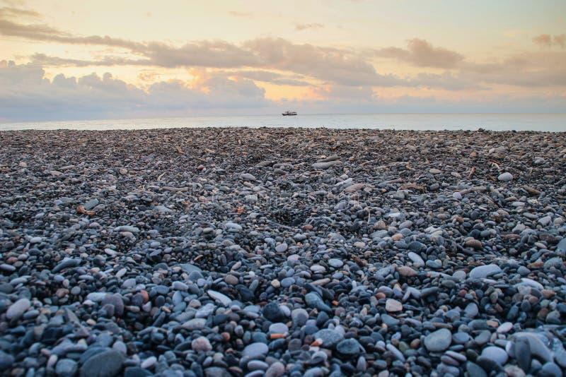 Overzeese grijze kiezelstenen op de kust en de gele zonsondergang stock afbeelding