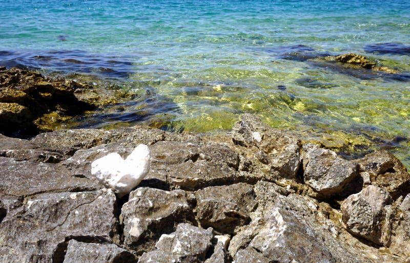 Overzeese kust met interessante stenen en rotsen op het voor en turkooise en blauwe zeewater op de achtergrond royalty-vrije stock afbeeldingen