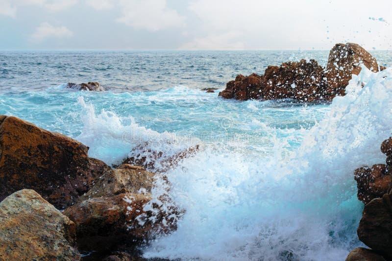 Overzeese landschap, golf en rotsen Stormachtige golven die in rotsen verpletteren royalty-vrije stock foto
