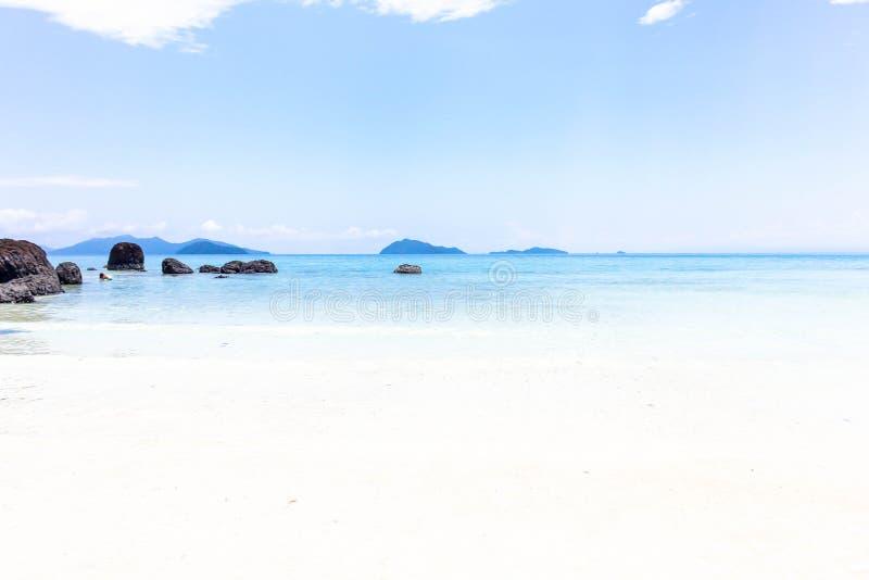 Overzeese mening van grote donkere steen en wit zand met blauwe hemel in Thai royalty-vrije stock fotografie