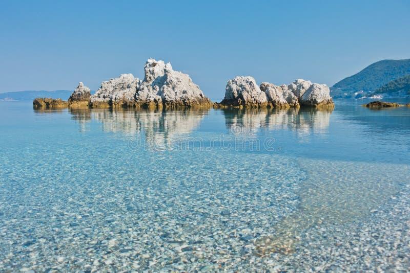Overzeese rotsen bij kalm en glashelder turkoois water bij ochtend, Milia-strand, Eiland Skopelos stock afbeelding