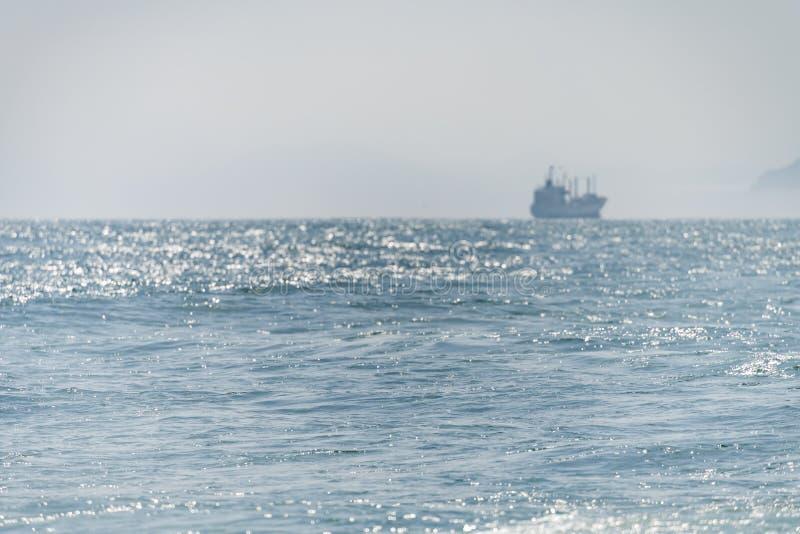 Overzeese schipzeilen Langs de kust bij zonlicht stock afbeeldingen
