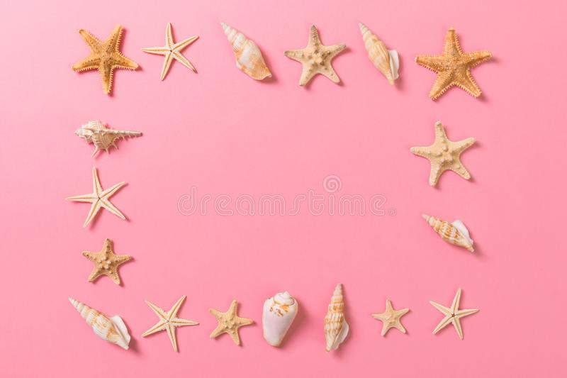 Overzeese shells en zeester op een roze achtergrond en een zand De tijdconcept van de vakantie royalty-vrije stock foto's