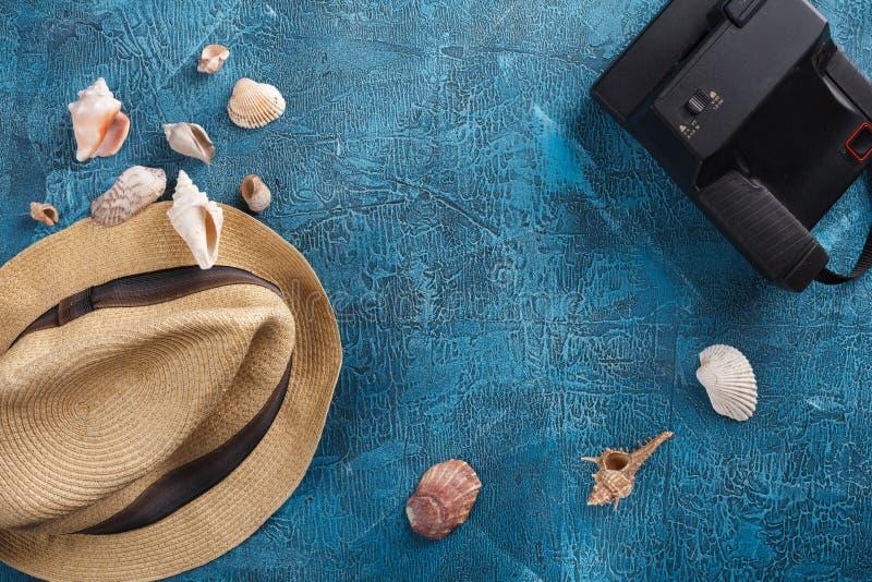 Overzeese shells, strandhoed en fotocamera op blauwe houten achtergrond royalty-vrije stock afbeelding