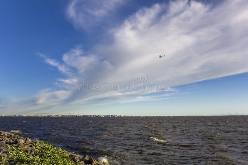 Overzeese steendijk en sterke wind over de golven tegen de achtergrond van de stad en een helikopter in de hemel met zware wolken stock afbeelding