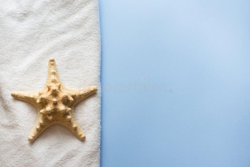 Overzeese ster en handdoek voor bad en kuuroord op blauwe achtergrond de zorgconcept van de lichaamshuid De ruimte van het exempl royalty-vrije stock afbeeldingen