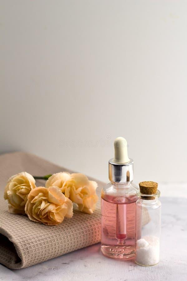 Overzeese van de aromaolie zoute flessen verse bloemen op handdoek marmeren lijst stock fotografie