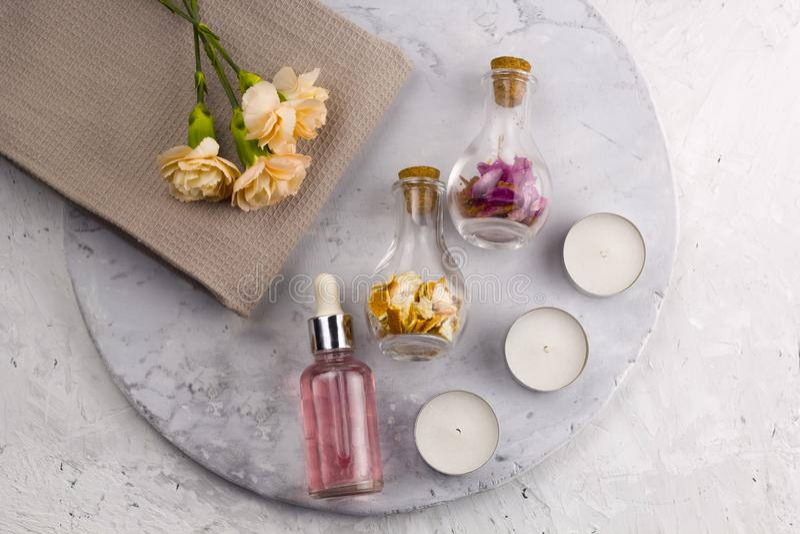 Overzeese van de aromaolie zoute flessen verse bloemen op handdoek marmeren lijst royalty-vrije stock fotografie