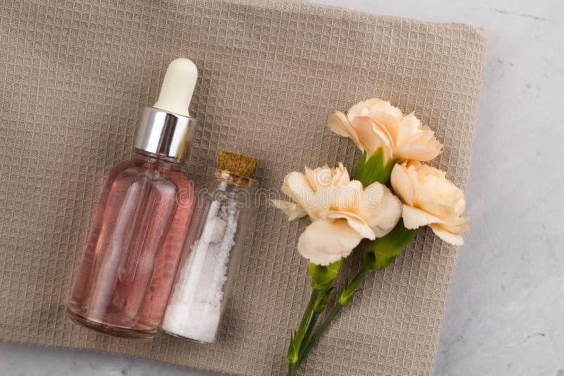 Overzeese van de aromaolie zoute flessen verse bloemen op handdoek marmeren lijst royalty-vrije stock afbeeldingen