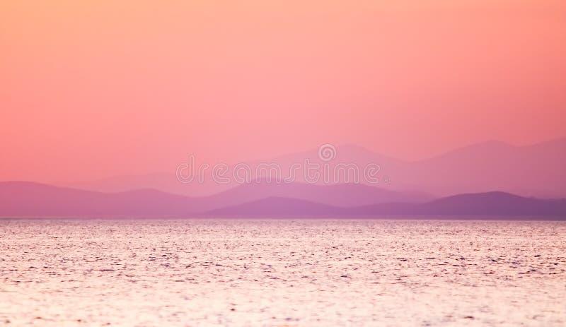 Overzeese zonsondergang met bergen op de achtergrond - Zachte nadruk stock fotografie