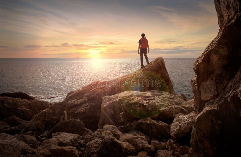 Overzeese zonsondergangmening Mens met rugzak op de rotsen royalty-vrije stock foto