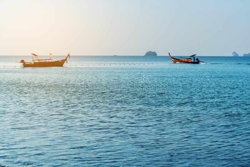 Overzeese zonsopgang of zonsondergang met vissersboot in ochtendlicht stock foto