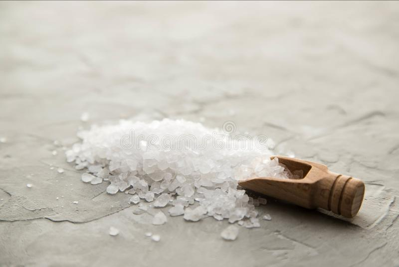 Overzeese zoute kristallen in houten lepelclose-up op concrete achtergrond Kleine schop met overzees zout Plaats voor tekst stock foto