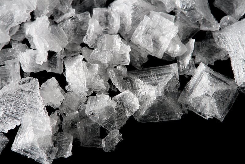 Overzeese zoute kristallenvlokken op zwarte achtergrond stock foto