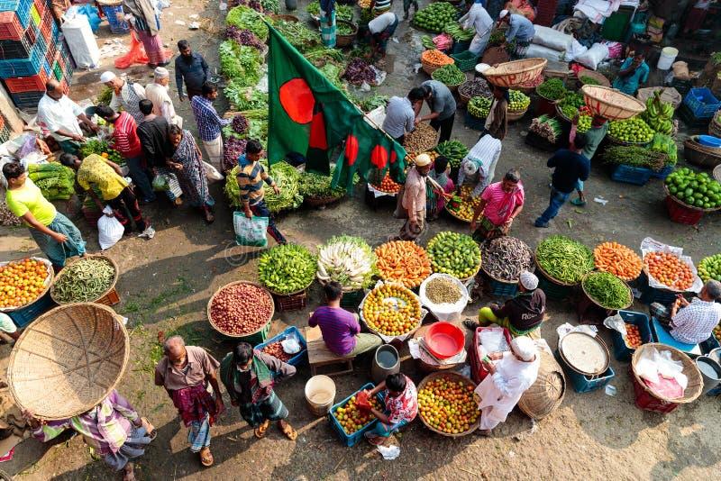 Overzicht van de straatscène bij een lokale plantaardige markt die in Dhaka, Bangladesh colorfull vruchten en kruiden tonen stock afbeeldingen
