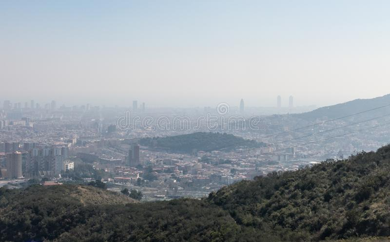 Overzicht van de verontreinigde stad van Barcelona, van de Collserola-berg, met een laag van smog over het royalty-vrije stock foto