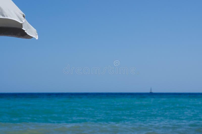 Overzicht van het overzees vaag van onder een strandparaplu door s stock foto's