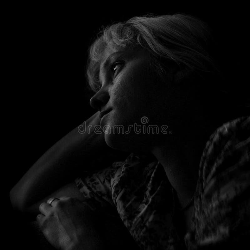Overzichten van een jonge woman& x27; s gezicht in de duisternis royalty-vrije stock afbeeldingen
