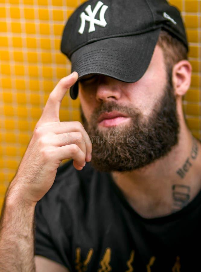 Oviedo Asturias SPANIEN - JULI 5, 2018 Ståenden av en ung hipster tatuerade mannen med New York Yankeeshatten royaltyfri fotografi