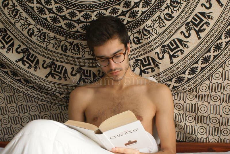 Oviedo, Aturias Spanien - 29 Agost 2018 Porträt einer hemdlosen Lesung des jungen normalen Mannes das Buch das lange Auf Wiederse stockfoto