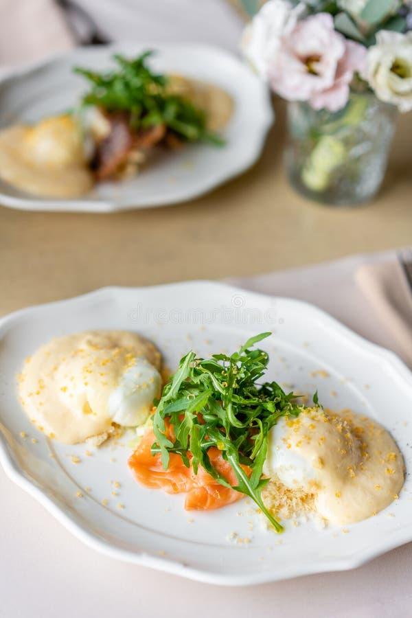 Ovo Benedict com pouca salada na placa com salmões e rúcula Molho delicioso do hollandaise de dois ovos Manhã clara fotos de stock