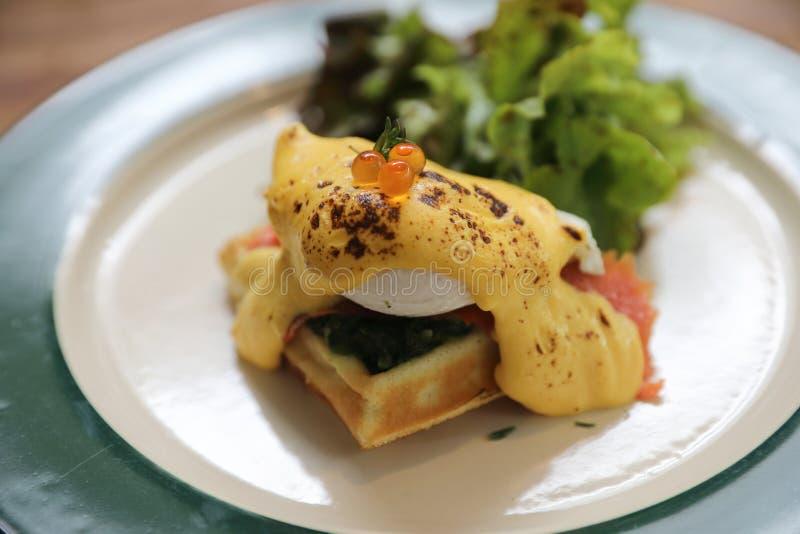 Ovo Benedict do alimento de café da manhã, ovo escalfado com molho amarelo com waffle e salmão fumado em um prato fotografia de stock royalty free