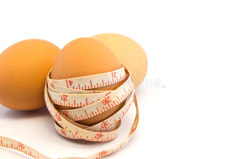 Ovo com fita métrica no fundo branco. imagens de stock