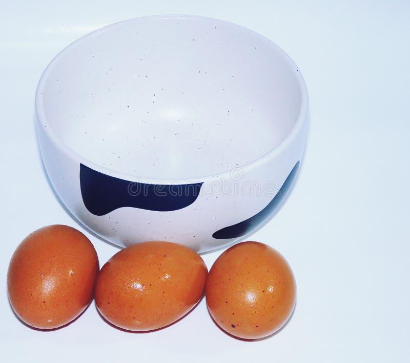 Ovo da galinha e bacia cerâmica, fundo branco imagens de stock