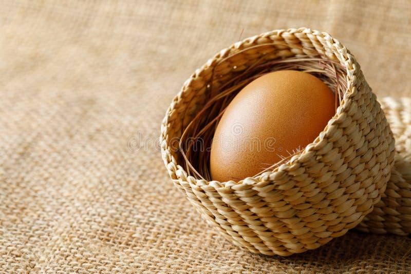 Ovo da galinha ou de galinha na cesta de vime no pano de saco imagens de stock