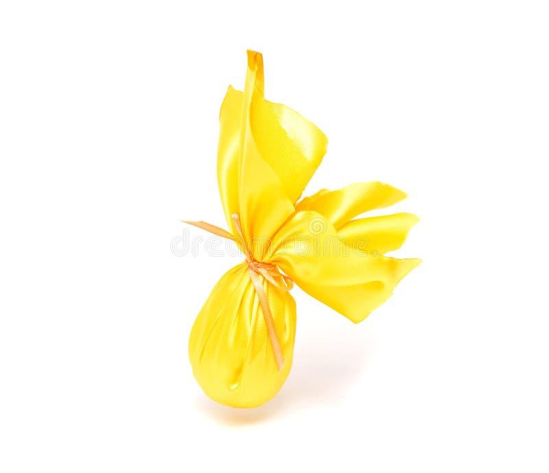 Ovo da páscoa amarelo envolvido com o pano amarelo do presente no fundo branco, isolado, conceito do presente de época natalícia  imagens de stock royalty free