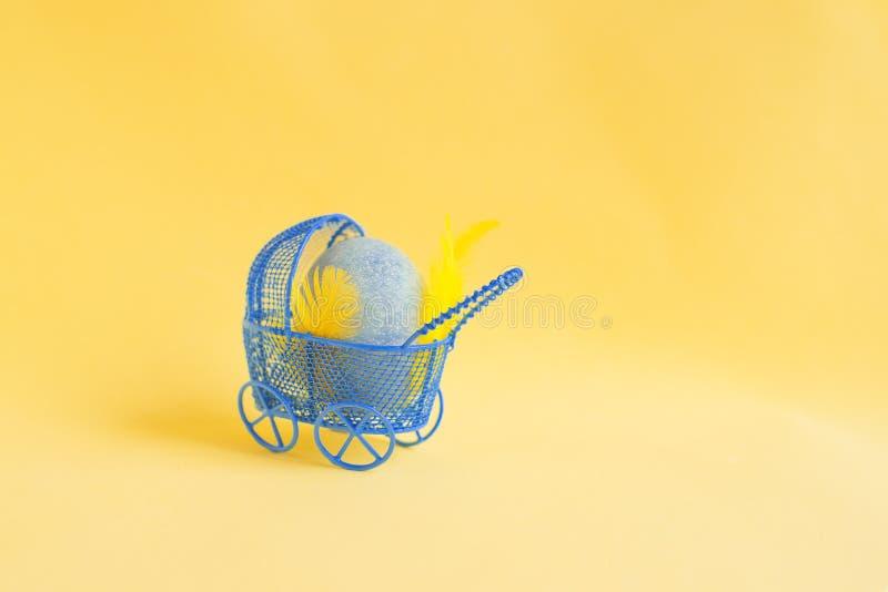 Ovo da páscoa azul em um transporte de bebê azul em um fundo amarelo foto de stock royalty free