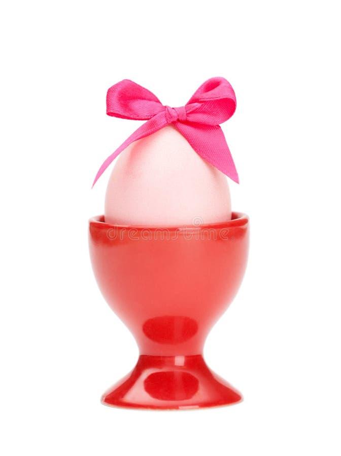 Ovo da páscoa com curva cor-de-rosa no copo de ovo vermelho fotos de stock