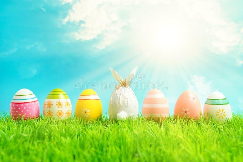 Ovo da páscoa envolvido em um papel na forma de um coelho com os ovos da páscoa coloridos na grama verde Conceito dos feriados da foto de stock