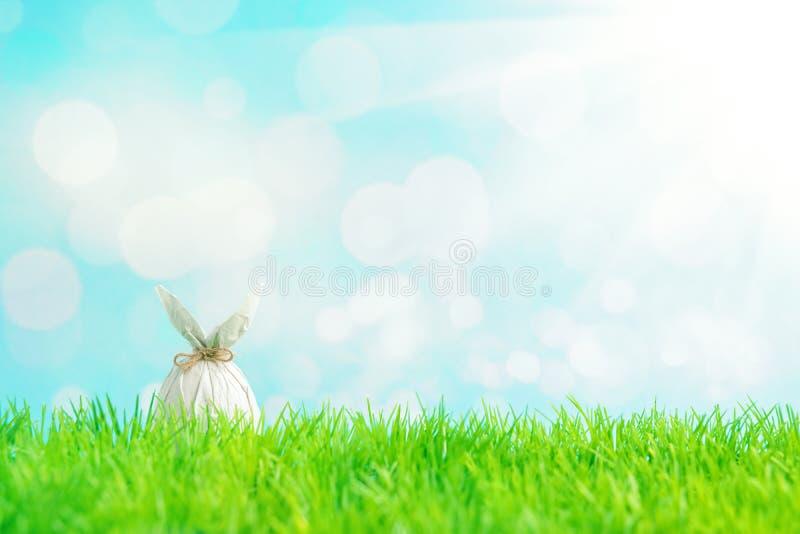 Ovo da p?scoa envolvido em um papel na forma de um coelho na grama verde Conceito dos feriados da mola fotografia de stock