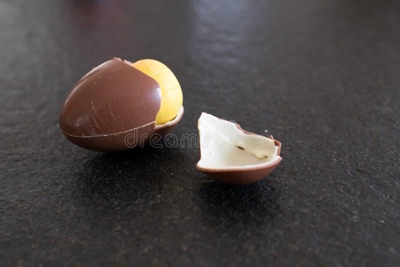 Ovo da páscoa para crianças com surpresa amarela para dentro Chocolate e imagens de stock royalty free