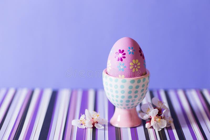 Ovo da páscoa pintado colorido do close up no suporte de ovo moderno vibrante cercado por ramos de árvore da florescência bran foto de stock